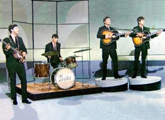 The Beatles on stage with guitar